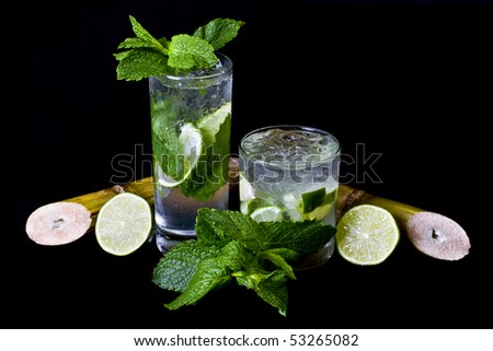 Mojito and Caipirinha over black background, garnished with mint leaves, lemon and Sugar cane.