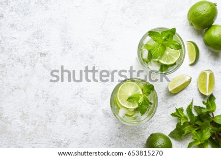 Mojito cocktail alcohol bar long drink traditional Cuba fresh tropical beverage top view copy space two highball glass, with rum, spearmint, lime juice, soda water and ice on white concrete table. #653815270