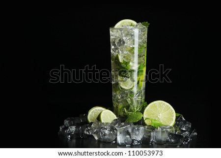 Mojito cocktail on black background with ice cubes