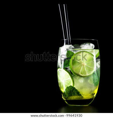 Mojito cocktail on black background with lime and mint with copy space