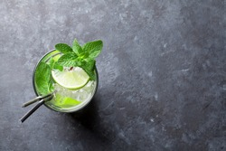 Mojito cocktail on dark stone table. Top view with space for your text