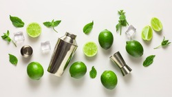 Mojito lime set, flat lay on white background. Concept: Mojito Cocktail. Whole juicy limes with ice and cocktail shaker. Concept: summer refreshing cocktail.