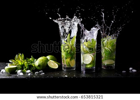 Mojito summer beach refreshing tropical cocktail splash in glass highball alcohol drink with soda water, lime juice, mint leaves, sugar, ice and rum. Dark black background with copy space text #653815321