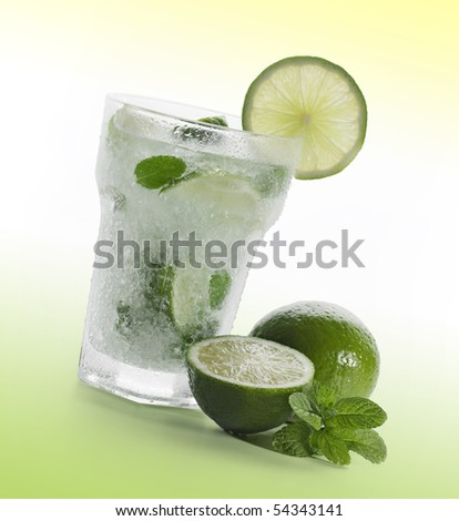 Mojito with limes and mint on green background