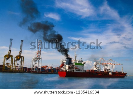 Molass red cargo vessel is running out of port. Black smoke ejected from the exhaust. Molass full in vessel