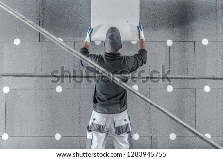 Molded Graphite Polystyrene House Insulation by Caucasian Contractor Worker. #1283945755