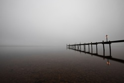 """Mole (pier) on the """"Chiemsee"""" lake in Bavaria, Germany. Wooden bridge in winter time with frozen and icy lake and dim lanterns for fishing. Dark and Foggy lake."""