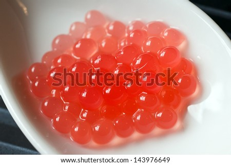 Molecular melon caviar balls on spoon