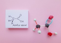 Molecular structure model and structural chemical formula of acetic acid molecule. Acetic acid (CH3COOH) is a colourless liquid organic compound with antibacterial properties. Black=C, red=O, white=H.