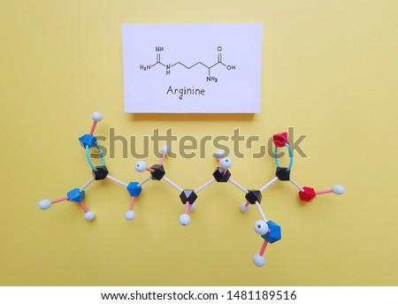 Molecular structure model and structural chemical formula of Arginine molecule. Arginine (L-arginine, Arg, R) is an α-amino acid that is used in the biosynthesis of proteins. Black=C, red=O, blue=N.