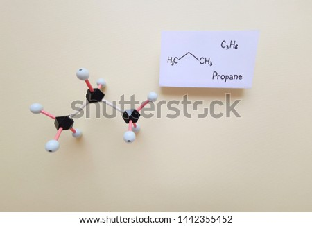Molecular structure model and structural chemical formula of propane molecule. Propane uses as liquefied petroleum gas, a fuel for engines, oxy-gas torches, barbecues etc. Black=C, white=H.