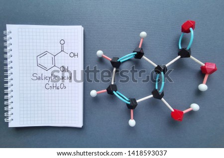 Molecular structure model and structural chemical formula of salicylic acid molecule. It is a type of phenolic acid. Used in cosmetics, in dermatological medicines, etc. Black=C, red=O, white=H.