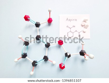 Molecular structure model of acetylsalicylic acid (aspirin, ASA) with tablets on bright background - C9H8O4. Structural chemical formula of aspirin written on the paper. Black=C, white=H, red=O. #1396851107