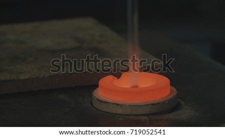 Molten Gold being poured into Ingot moulds. Molten Gold being poured into Ingot moulds. Casting metal or gold being poured into molds in foundry #719052541
