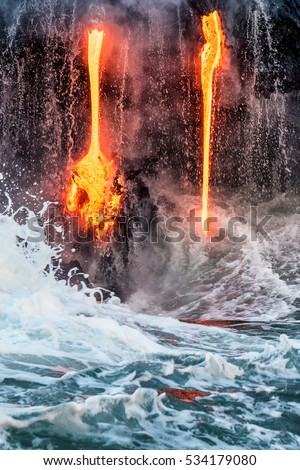 Molten lava flowing into the Pacific Ocean on Big Island of Hawaii at sunrise, with water and lava flowing down lava rock wall as waves crash as seen from a tour boat