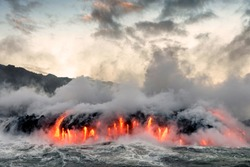 Molten lava from Kilauea volcano flowing into the Pacific Ocean on Big Island of Hawaii