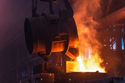 Molten metal is poured with sparks from ladle into mold. Smelting of multi-ton cast iron parts in foundry. Metallurgical plant or Steel Mill
