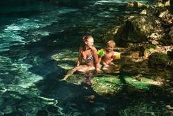 Mom and a boy in the Dos Ojos cenote, Tulum, Quintana Roo, Mexico