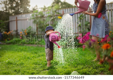 Mom and boy child water the garden together, Mom's little gardener assistant, taking care of children and garden. Mother watering her son from watering can, take care of trees and plants, wet child