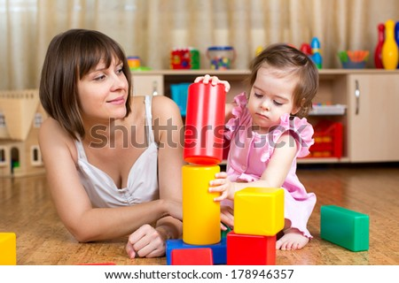 mom and child play block toys indoors