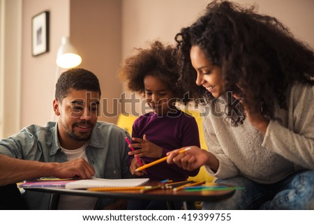Mom and dad drawing with their daughter.