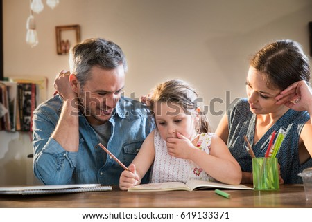Mom and Dad help their little girl do homework for school #649133371