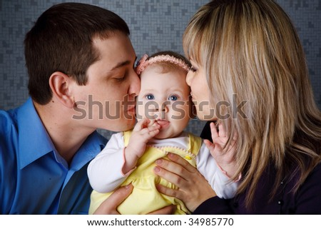 mom and dad kiss their daugther