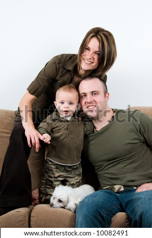 mom and dad on a sofa with their baby boy