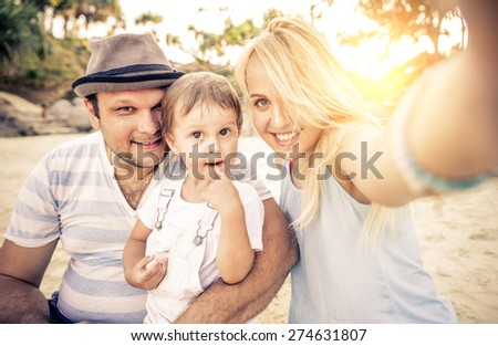 Mom and dad playing with their handsome son - Family and baby outdoors - Young beautiful mother taking a self portrait with her family