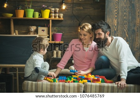 Mom and dad watch son playing with construction blocks. Side view blond kid sitting on the edge of sofa. Happy family in playroom. #1076485769
