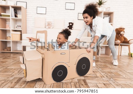 Mom and daughter are playing with big toy cars. They are at home. African American girl and a woman.
