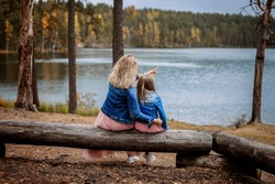 Mom and daughter are sitting on a log on the shore of a forest lake. Mom points into the distance. They wear the same clothes - family look