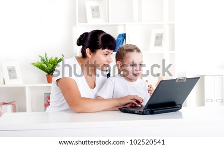 Mom and daughter are working together for a laptop at home