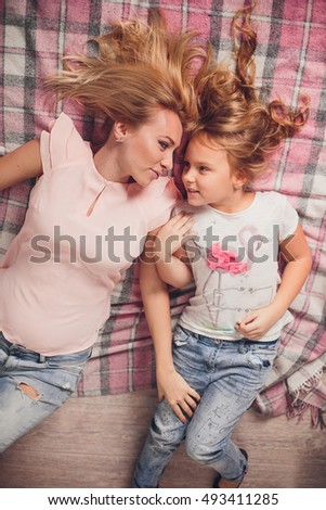 Mom and daughter blonde caucasians are happy and smiling on a pink checked plaid on the floor. Happy beautiful family. Mothers Day #493411285