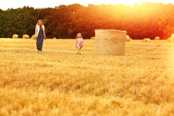 Mom and daughter Caucasians walk with a smile on a mown wheat field where there are huge sheaves. Family fun and fun. Nature. Harvesting. Agriculture. Cereals. Rural life. Rest in the countryside.