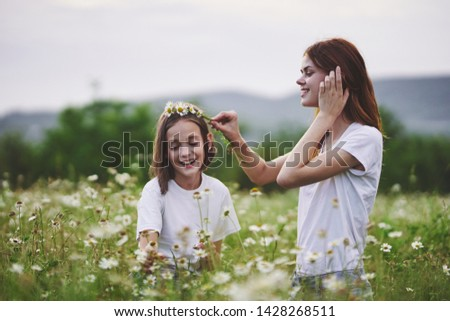 Mom and daughter collect chamomile flowers leisure leisure nature games
