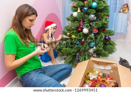 Mom and daughter decorate the Christmas tree