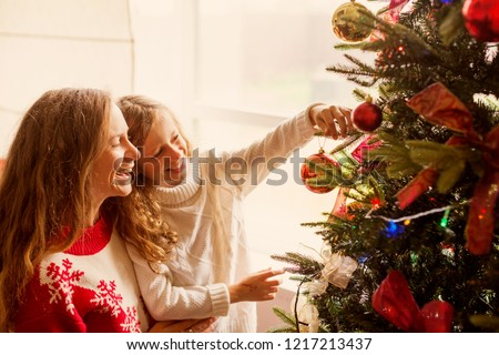 Mom and daughter decorate the Christmas tree. Happy family at home