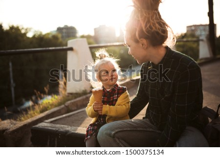 mom and daughter eat ice cream on a city street, mom and daughter play with ice cream, have fun walking around the city together. Caucasian mom hipster with dreadlocks with her blonde toddler daughter #1500375134