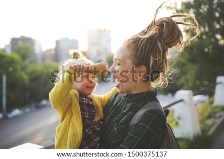 mom and daughter eat ice cream on a city street, mom and daughter play with ice cream, have fun walking around the city together. Caucasian mom hipster with dreadlocks with her blonde toddler daughter #1500375137