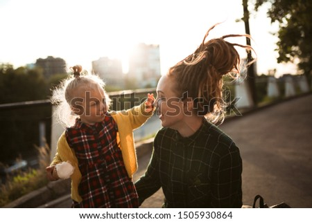 mom and daughter eat ice cream on a city street, mom and daughter play with ice cream, have fun walking around the city together. Caucasian mom hipster with dreadlocks with her blonde toddler daughter #1505930864