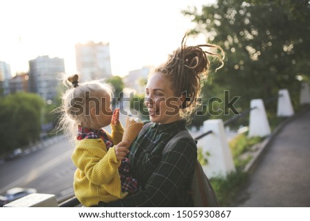 mom and daughter eat ice cream on a city street, mom and daughter play with ice cream, have fun walking around the city together. Caucasian mom hipster with dreadlocks with her blonde toddler daughter #1505930867