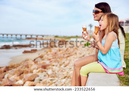 Mom and daughter enjoy fun ice cream at the beach smiling laughing joy on summer vacation - stock photo