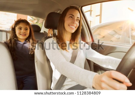 Mom and daughter going to the school in the car - Shutterstock ID 1128384809