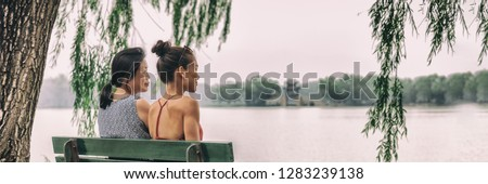 Mom and daughter happy relaxing together at Beijing summer palace lake park enjoying quiet summer day traveling in China. Two women relaxing peaceful on park bench. Asian women, banner panorama.