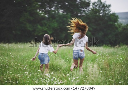 mom and daughter hold hands walk on the field countryside countryside fun