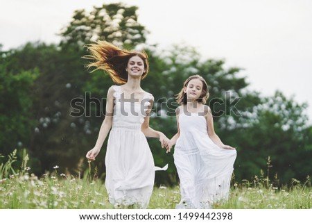 Mom and daughter in white dresses nature fun leisure leisure #1499442398