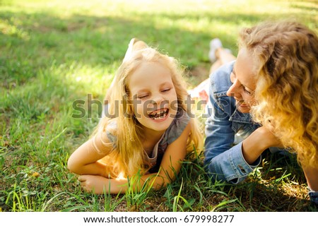 Mom and daughter lie on the grass in the park