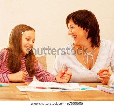 Mom and daughter painting on paper - family