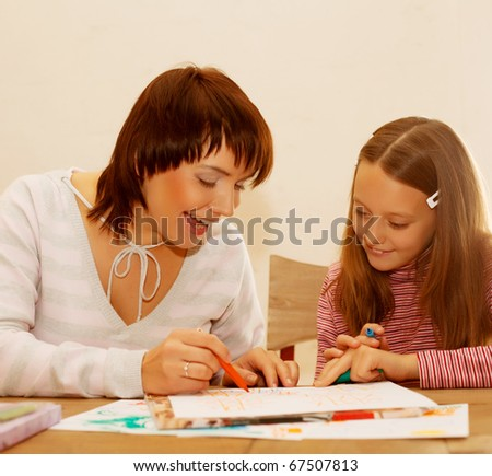 Mom and daughter painting on paper. Happy family.